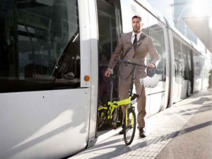 Business man exiting train with foldaway bike